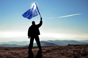 successfull silhouette man winner waving Europian Union flag on top of the mountain peak